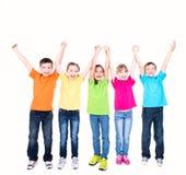 Grupp av att le ungar med lyftta händer. Fotografering för Bildbyråer