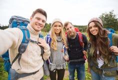 Grupp av att le vänner med att fotvandra för ryggsäckar Arkivfoton