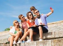 Grupp av att le vänner med smartphonen utomhus Arkivbild