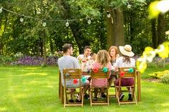 Grupp av att le vänner som tycker om det utomhus- födelsedagpartiet under arkivbilder