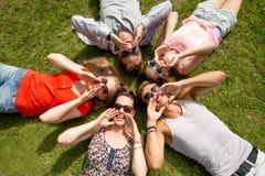 Grupp av att le vänner som utomhus ligger på gräs Fotografering för Bildbyråer