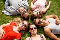 Grupp av att le vänner som utomhus ligger på gräs Arkivbild