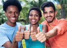 Grupp av att skratta afrikansk amerikan- och latinman- och kvinnavisningtummen Fotografering för Bildbyråer