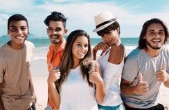 Grupp av att skratta den latinska caucasianen och afrikansk amerikanmän och kvinna på stranden Royaltyfria Bilder
