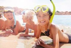 Grupp av att skratta ungar i dykapparatmaskering på stranden Fotografering för Bildbyråer