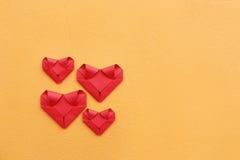 grupp av att vika röda pappers- hjärtor på den gula betongväggen för PA Arkivbilder
