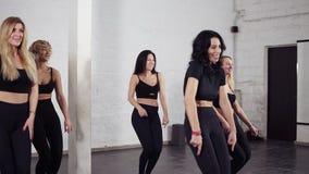 Grupp av attraktiva sexiga kvinnor som lär handflyttningar av bachatadansen Dansa grupp