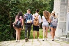 Grupp av attraktiva tonårs- studenter som går från universitet arkivbilder