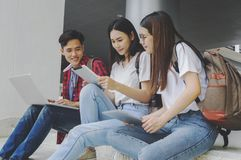 Grupp av attraktiva ungdomarsom använder en bärbar dator och en minnestavla, sitt arkivbild