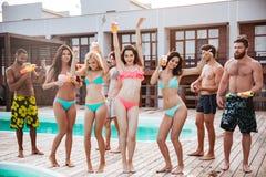 Grupp av bästa vän som har gyckel på simbassängen fotografering för bildbyråer