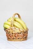 Grupp av bananer i korg Arkivfoto