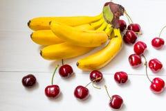 Grupp av bananer och spillda körsbär Arkivfoton