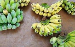 Grupp av bananer på den wood tabellen Fotografering för Bildbyråer