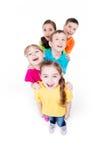 Grupp av barn i färgrikt t-skjortor stå. Arkivbild