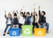 Grupp av barn med ett återvinningsymbol royaltyfri bild