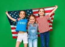 Grupp av barn med flaggan av Amerikas förenta stater USA på grön bakgrund royaltyfri fotografi