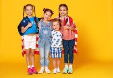 Grupp av barn med flaggan av Amerikas förenta stater USA på gul bakgrund fotografering för bildbyråer