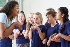 Grupp av barn med läraren Enjoying Drama Class tillsammans arkivbilder