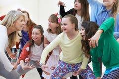 Grupp av barn med läraren Enjoying Drama Class tillsammans arkivfoto