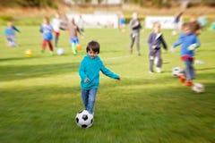 Grupp av barn och att spela fotboll som övar Arkivfoto