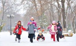 Grupp av barn och modern som spelar på insnöad vintertid Royaltyfria Bilder
