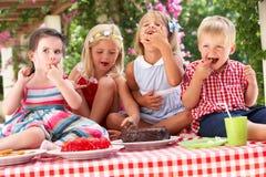 Grupp av barn som äter caken på den utomhus- Teadeltagaren Royaltyfri Fotografi