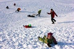 Grupp av barn som åka släde under ferier Arkivfoto
