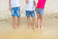 Grupp av barn som bär casaual grov bomullstvillkortslutningar som har roligt anseende på sand på stranden Tre litet barnvänner so arkivfoto