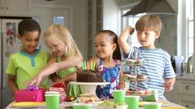 Grupp av barn som firar födelsedag med kakan och gåvor stock video