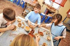 Grupp av barn som formar lera i krukmakeristudio Arkivbilder