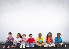 Grupp av barn som framme sitter av tom grå bakgrund royaltyfri fotografi