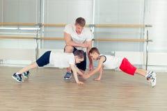 Grupp av barn som gör ungegymnastik i idrottshall med barnkammareteac arkivbild