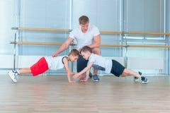 Grupp av barn som gör ungegymnastik i idrottshall med läraren Lyckliga sportiga barn i idrottshall stångövning planka royaltyfri fotografi