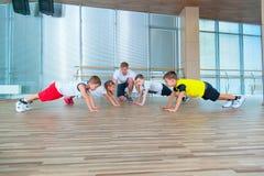Grupp av barn som gör ungegymnastik i idrottshall med läraren Lyckliga sportiga barn i idrottshall stångövning planka royaltyfria bilder