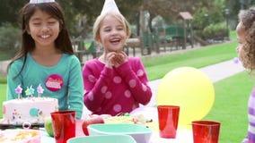 Grupp av barn som har det utomhus- födelsedagpartiet arkivfilmer