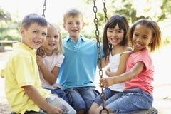Grupp av barn som har gyckel i lekplats tillsammans Arkivbilder