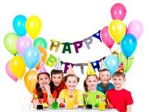 Grupp av barn som har gyckel på födelsedagpartiet Royaltyfri Foto