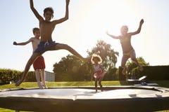 Grupp av barn som har rolig banhoppning på den utomhus- trampolinen royaltyfri foto