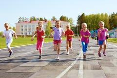 Grupp av barn som kör på trampkvarnen Arkivbild