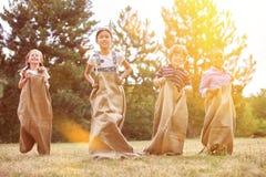 Grupp av barn som konkurrerar på säckloppet Arkivbild