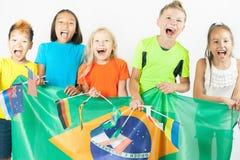 Grupp av barn som rymmer en Brasilien flagga Fotografering för Bildbyråer