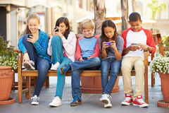 Grupp av barn som sitter i galleria genom att använda mobiltelefoner Arkivbilder