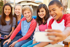 Grupp av barn som sitter på bänk i gallerian som tar Selfie arkivbild
