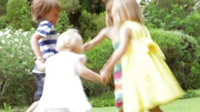 Grupp av barn som spelar den Ring Around The Rosy In trädgården stock video