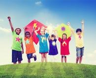 Grupp av barn som spelar drakar utomhus Royaltyfri Foto