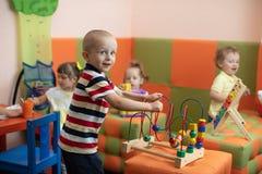 Grupp av barn som spelar i dagis- eller daycaremitt arkivbild