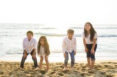 Grupp av barn som spelar på kanten av havet royaltyfri foto