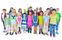 Grupp av barn som står i linjen kamratskapbegrepp Arkivbild