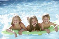 Grupp av barn som tillsammans kopplar av i simbassäng arkivbilder