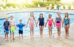 Grupp av barn som tillsammans spelar på simbassängen Arkivfoton